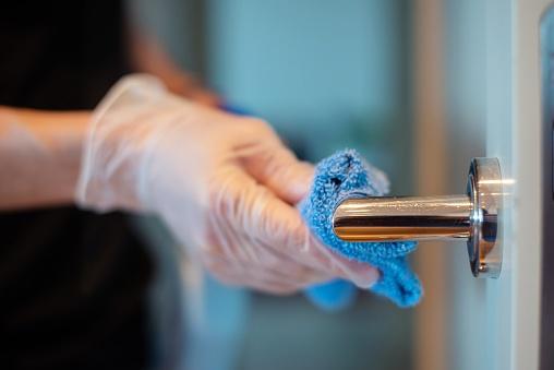 Camarero limpiador limpiando manilla de puerta